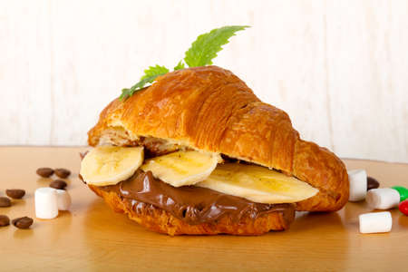 Croissant with chocolate and banana served leaf