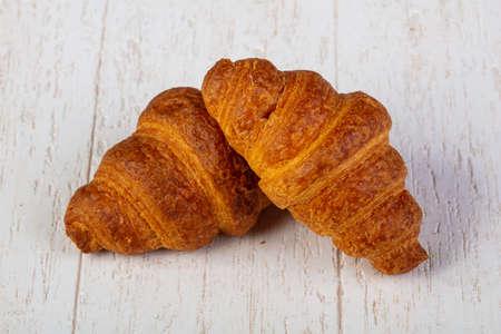 Sweet tasty croissant over wooden background 版權商用圖片