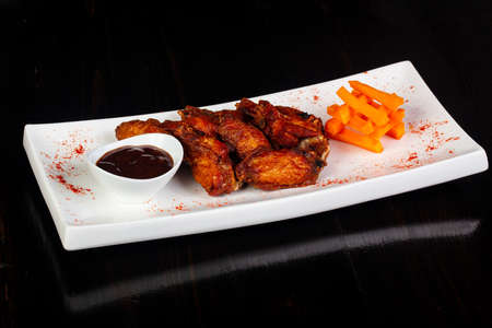 BBQ chicken wings with sauce and carrots Stock Photo