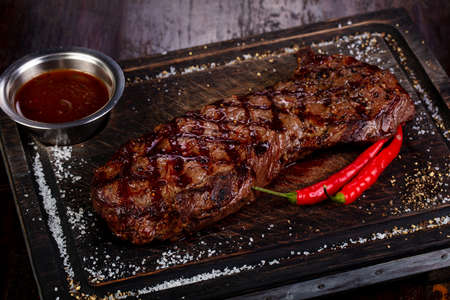 Grilled beef steak with sauce and pepper