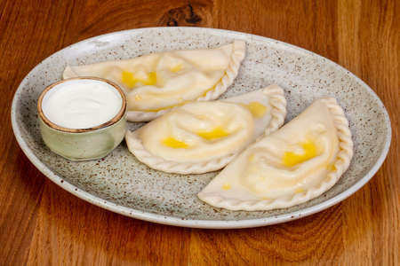 Ukrainian dumplings - vareniki with cream sauce