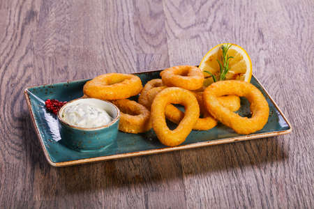 Squid rings with sauce served lemon