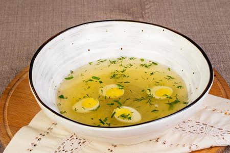 Light chicken soup with quail egg Фото со стока