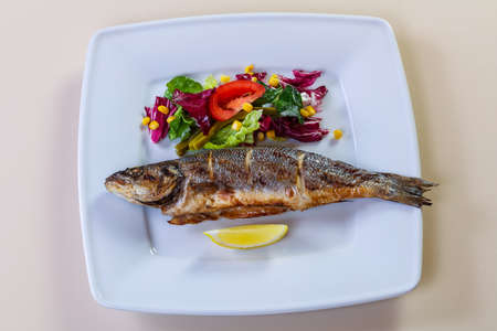 Grilled seabass with lemon and salad mix Archivio Fotografico