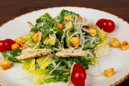 Caesar salad with chicken and cheese Фото со стока