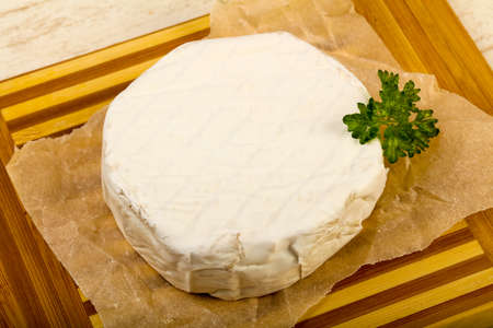 Camembert cheese with parsley over the wooden background Banco de Imagens