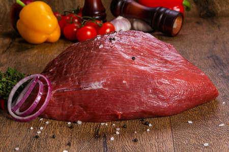 Raw beef meat over the wooden background Stockfoto