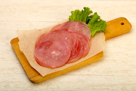 Sliced sausage with salad leaves