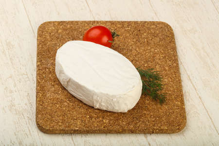 Camembert cheese over the wooden background