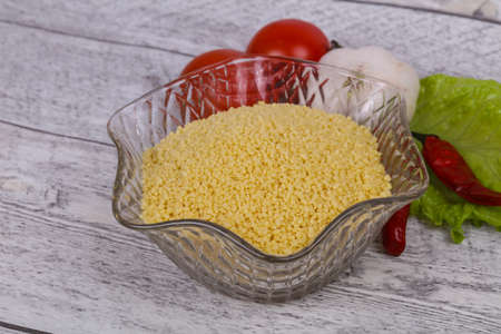 Raw couscous in the bowl served salad leaves, tomato and pepper ready for cooking