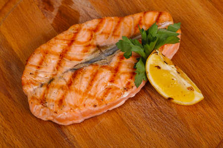 Grilled salmon served lemon and parsley over the wooden board