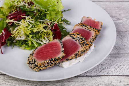 Salad with fresh sliced tuna in sesame seeds Фото со стока