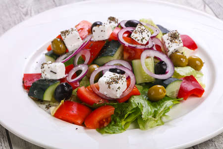Traditional Greek salad with feta cheese, vegetables and herbs