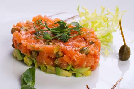Tartar de salmón y aguacate servido con alcaparras y balsámico