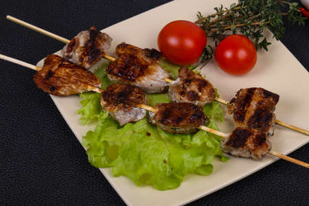 Pork kebab skewers in the plate with salad leaves and tomatoes served thyme and garlic