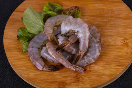 Raw king prawns ready for cooking served salad leaves