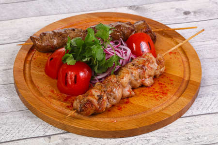 Chicken and beef skewers served gtillrf tomato and parsley