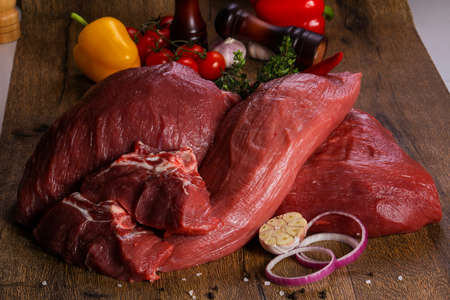 Raw beef meat over the wooden background Standard-Bild - 117307998