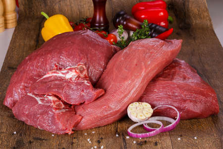 Raw beef meat over the wooden background Standard-Bild - 119000640