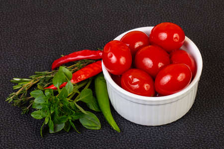 Pickled cherry tomato in the bowl served basil 写真素材