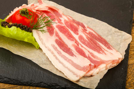 Raw bacon served dill over the wooden background Standard-Bild - 119973450
