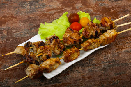 Tasty pork skewer bbq with salad leaves