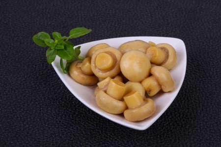 Pickled champignon heap in the bowl served basil leaves Reklamní fotografie
