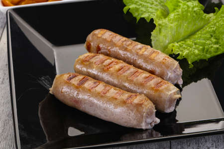 Grilled sausages served mushrooms, salad and cabbage