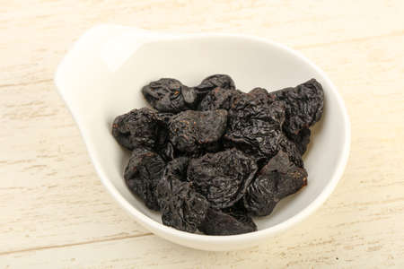 Dried plums heap in the bowl over wooden background