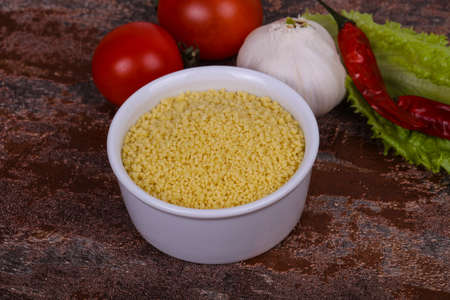 Raw couscous in the bowl served salad leaves, tomato and pepper ready for coocking