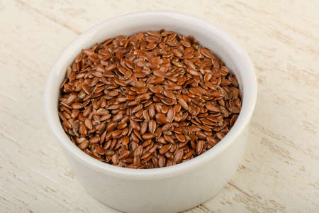 Fry Flax seeds heap in the bowl over wooden background