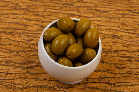 Green olives in the bowl over wooden bacground Фото со стока
