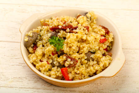 Bulgur with chicken hearts and dry tomatoes Foto de archivo