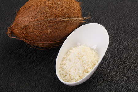 Coconut shredded chip with nut over wooden background