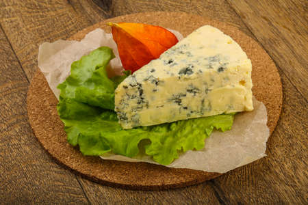 Blue cheese with salad leaves over the wooden background 免版税图像