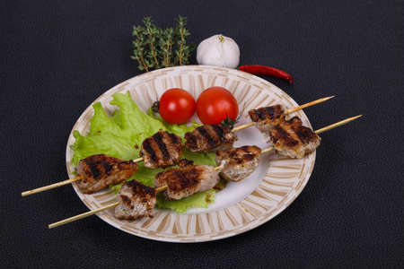 Pork kebab skewers in the plate with salad leaves and tomatoes served thyme and garkic