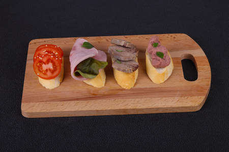 Bruschetta with tomato, ham and tongue served salad leaves and capers