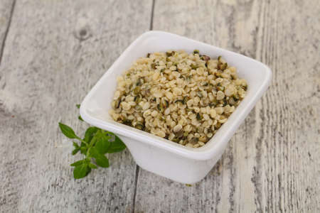 Peeled hemp seeds in the bowl over wooden background Stok Fotoğraf