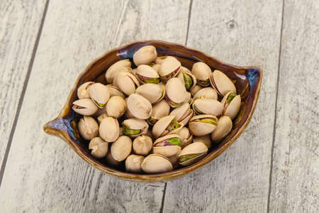 Pistachio nuts heap in the bowl Imagens