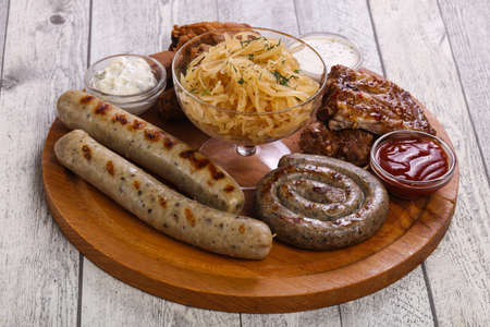 Meat plate with grilled sausages, ribs and chicken wings served cabbage Reklamní fotografie - 124906528