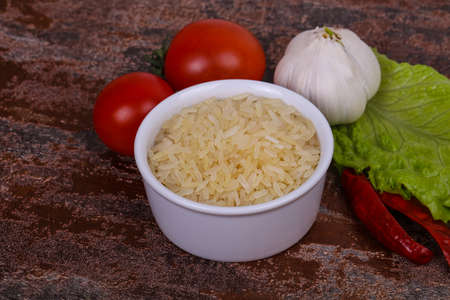 Raw uncooked rice in the bowl served pepper and salad leaves