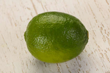Ripe green lime over the wooden background Imagens