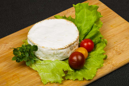 Delicious Camembert cheese with salad leaves Imagens