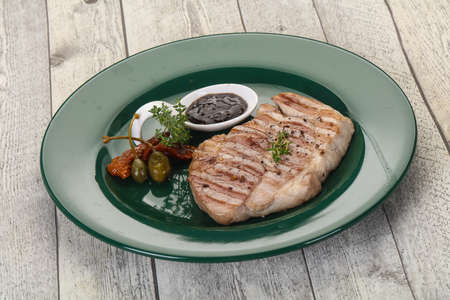 Grilled pork steak with pepper sauce served dried tomatoes and thyme
