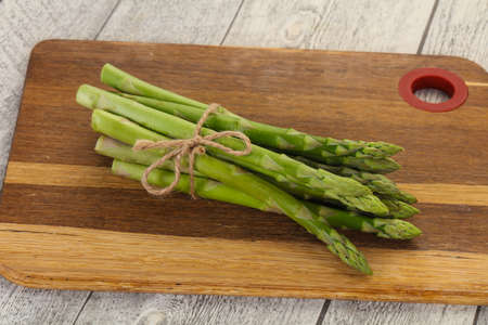 Raw asparagus heap over the wooden board