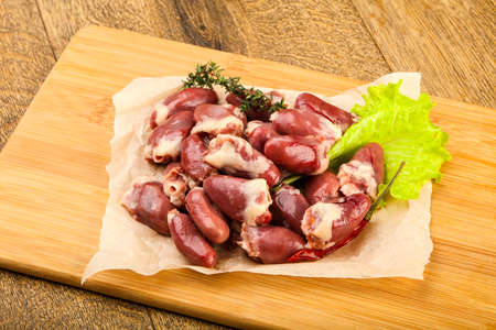 Raw chicken hearts heap with thyme branch