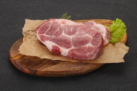 Raw pork steak over wooden board ready for cooking Stock Photo