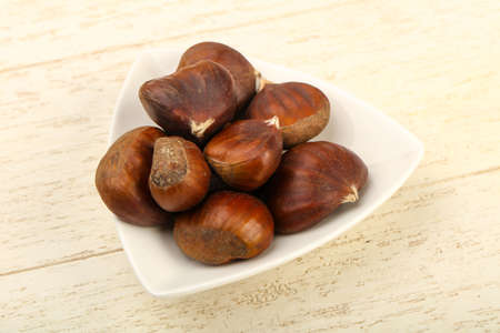 Chestnuts in the bowl over wooden background Imagens
