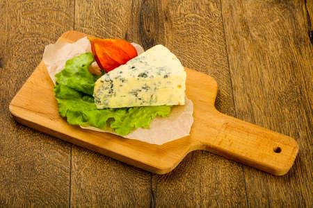 Blue cheese with salad leaves over the wooden background Zdjęcie Seryjne