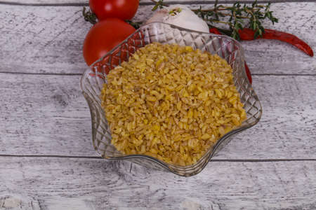 Raw golden bulgur in the bowl with tomatoes and garlic